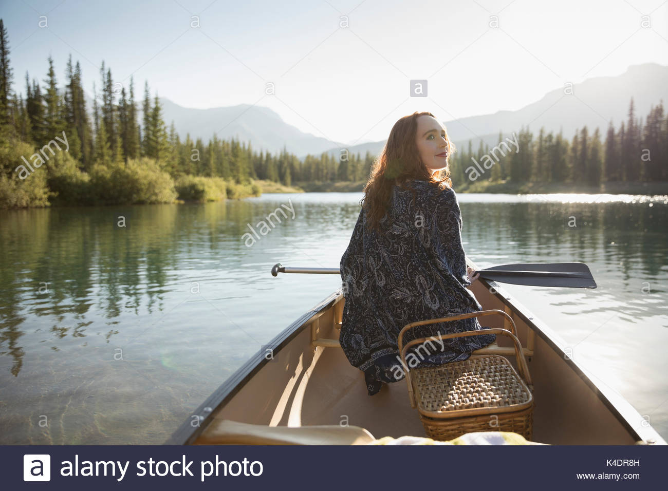 Serene woman with picnic basket holding oar in canoe on sunny summer lake - Stock Image