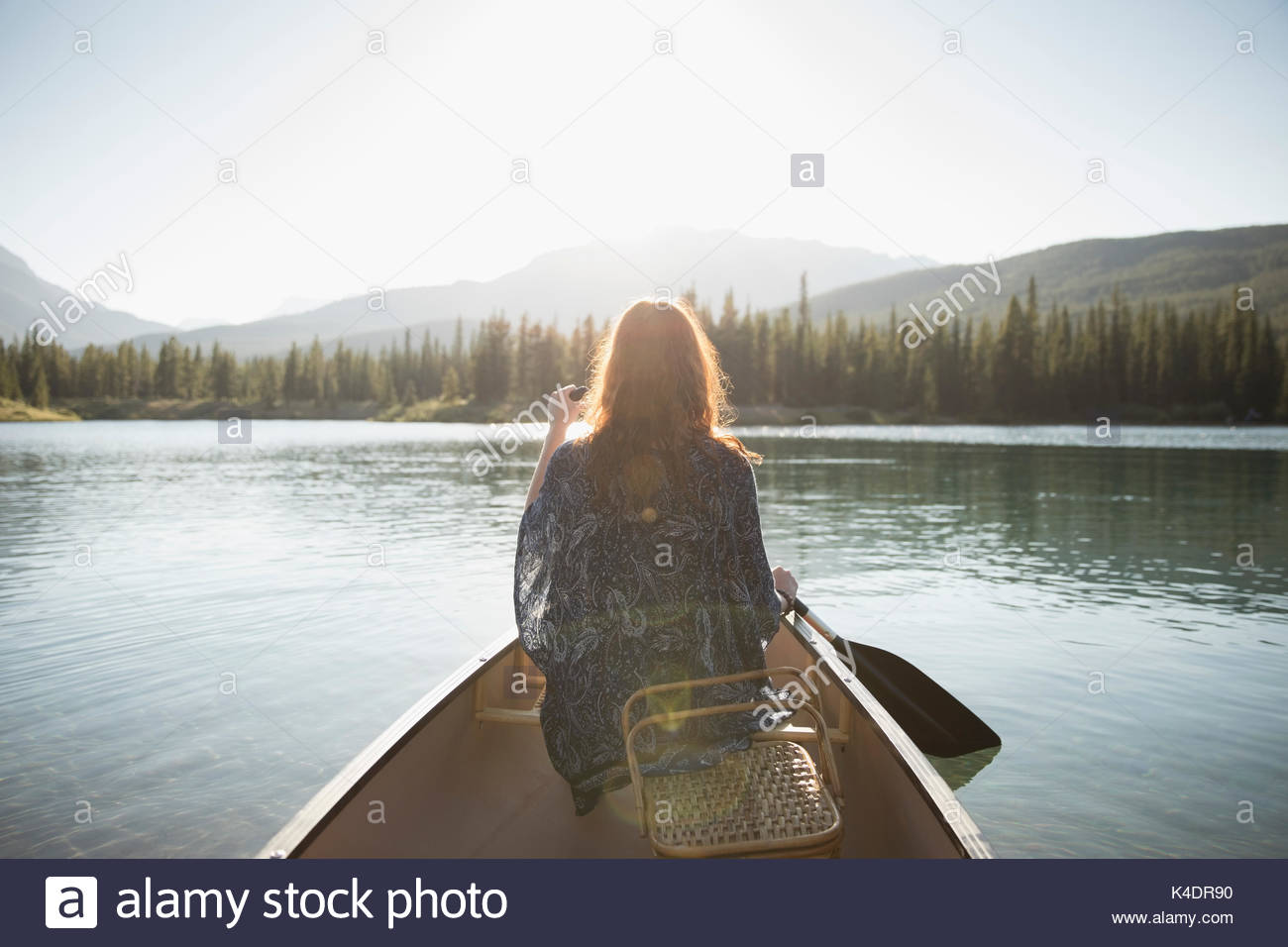 Woman with picnic basket paddling canoe with oar on sunny summer lake - Stock Image
