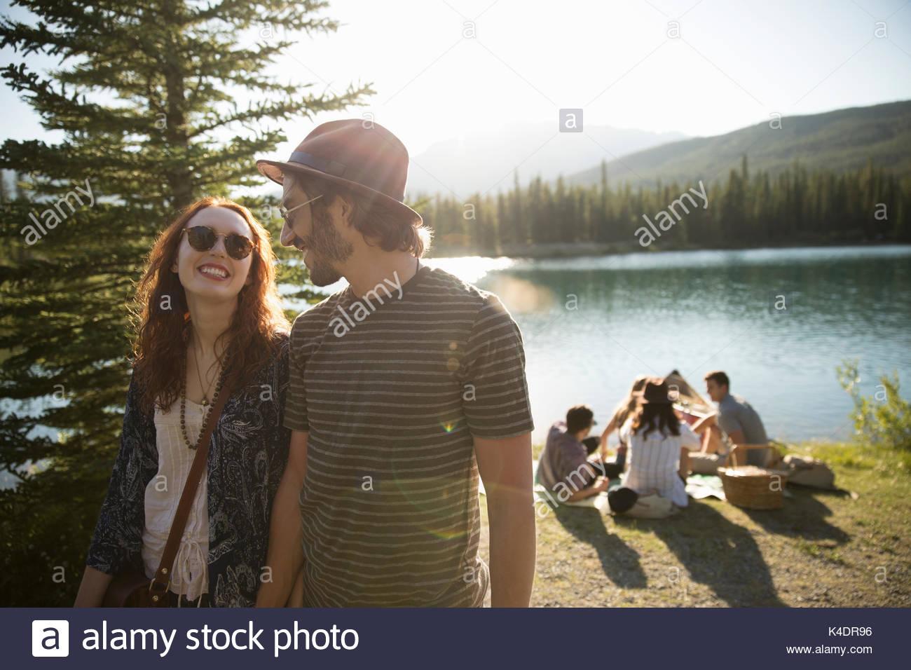 Affectionate couple walking at sunny summer lakeside - Stock Image