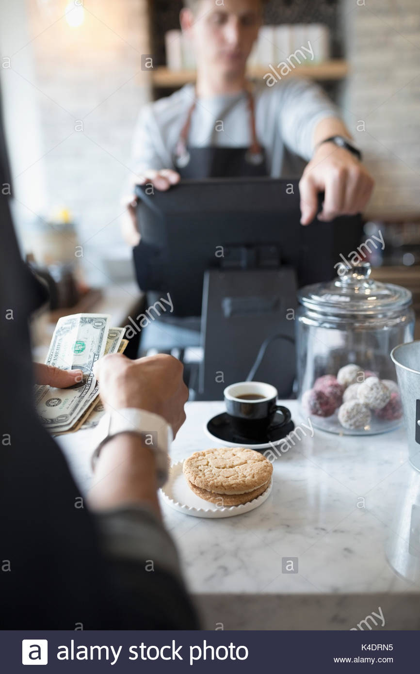 Customer paying with cash at cafe counter - Stock Image