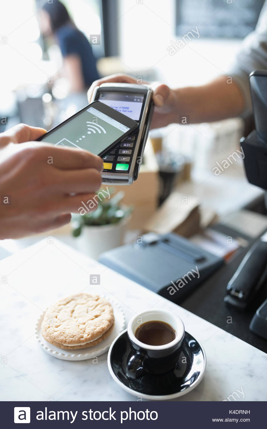 Customer paying with smart phone contactless payment at cafe - Stock Image