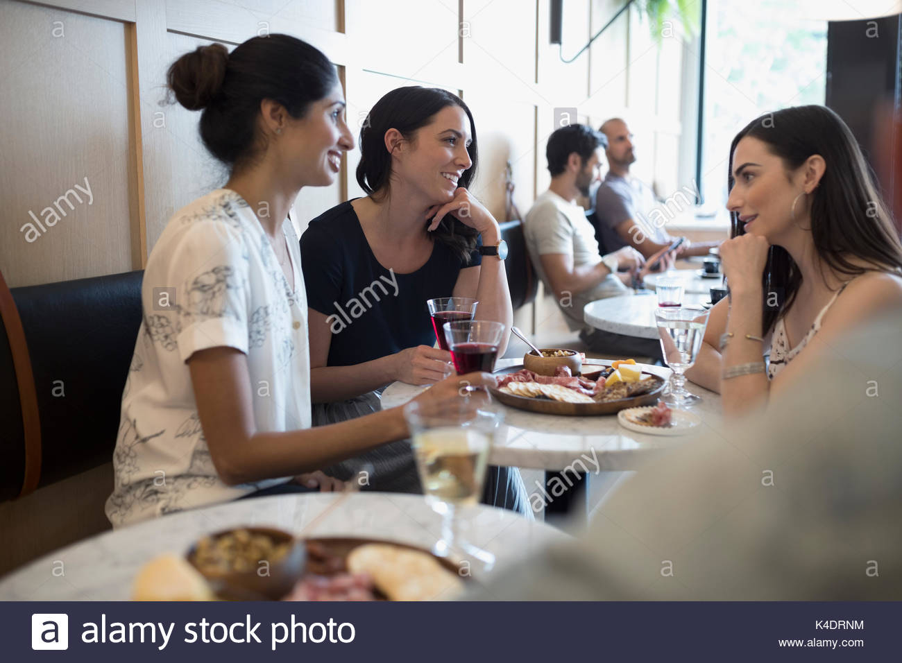 Women friends drinking wine at cafe table Stock Photo
