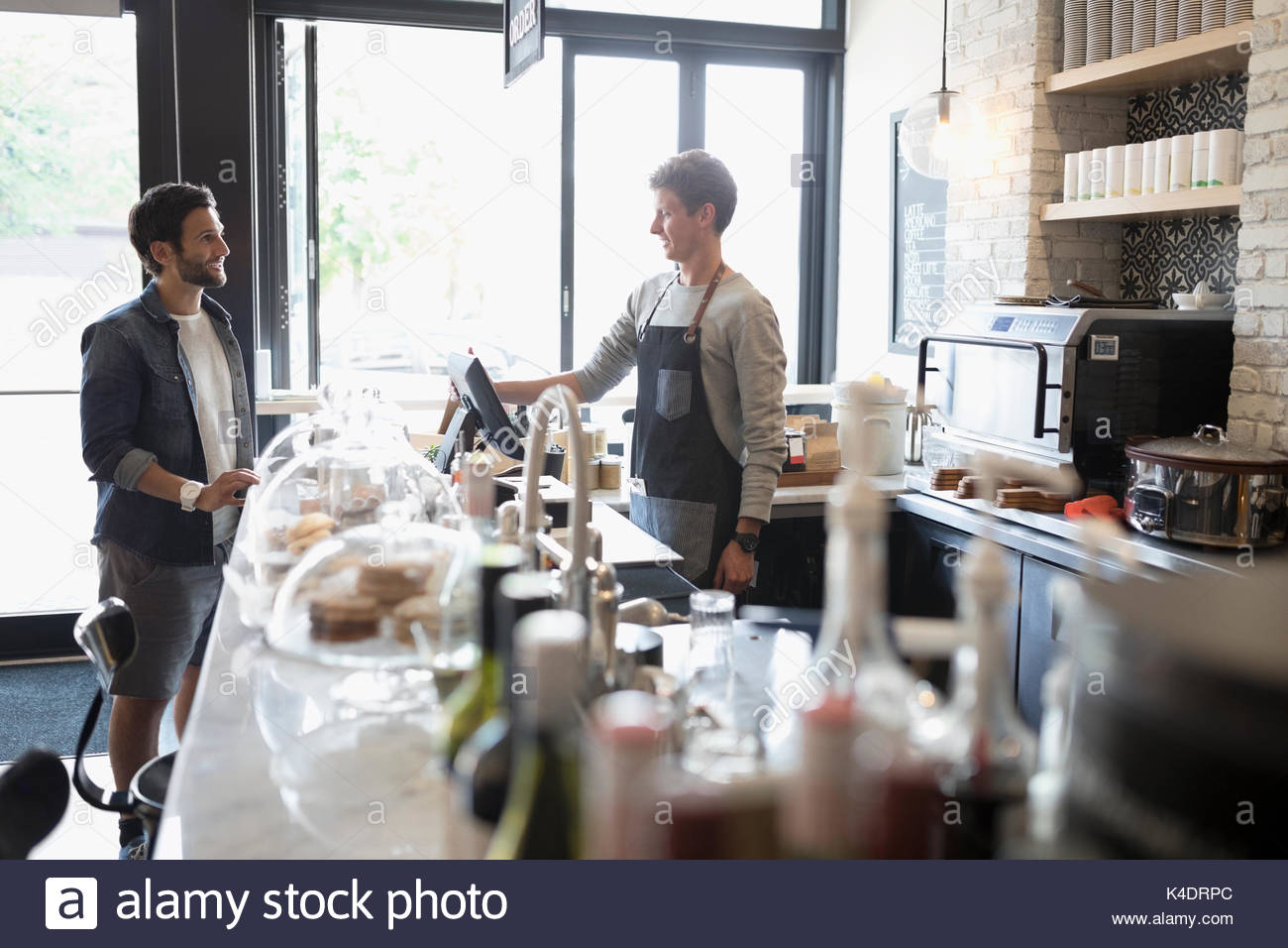 Male customer ordering from worker at cafe counter - Stock Image