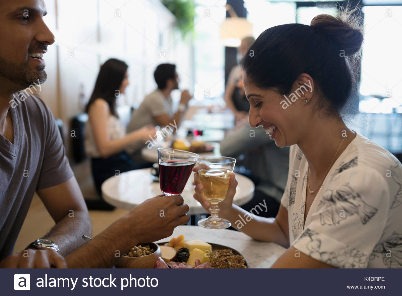 Happy couple toasting wine glasses at cafe table - Stock Image