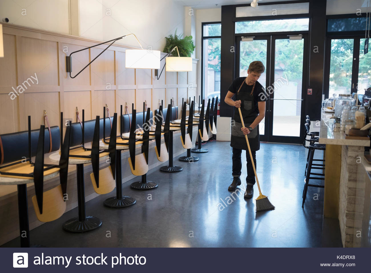 Male worker sweeping cafe with broom - Stock Image