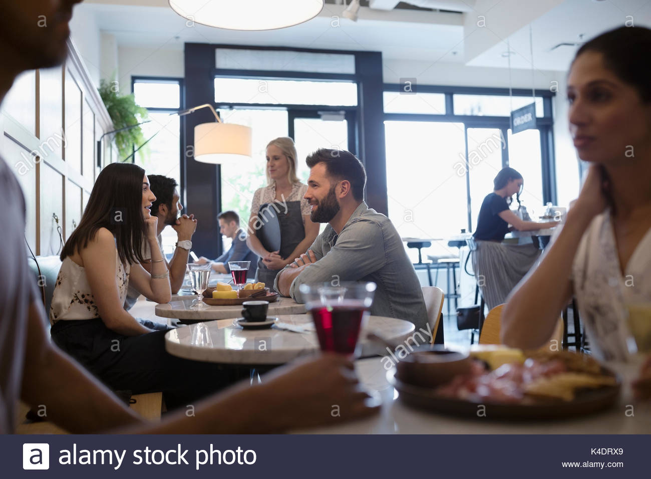 Customers eating and drinking wine at cafe tables Stock Photo