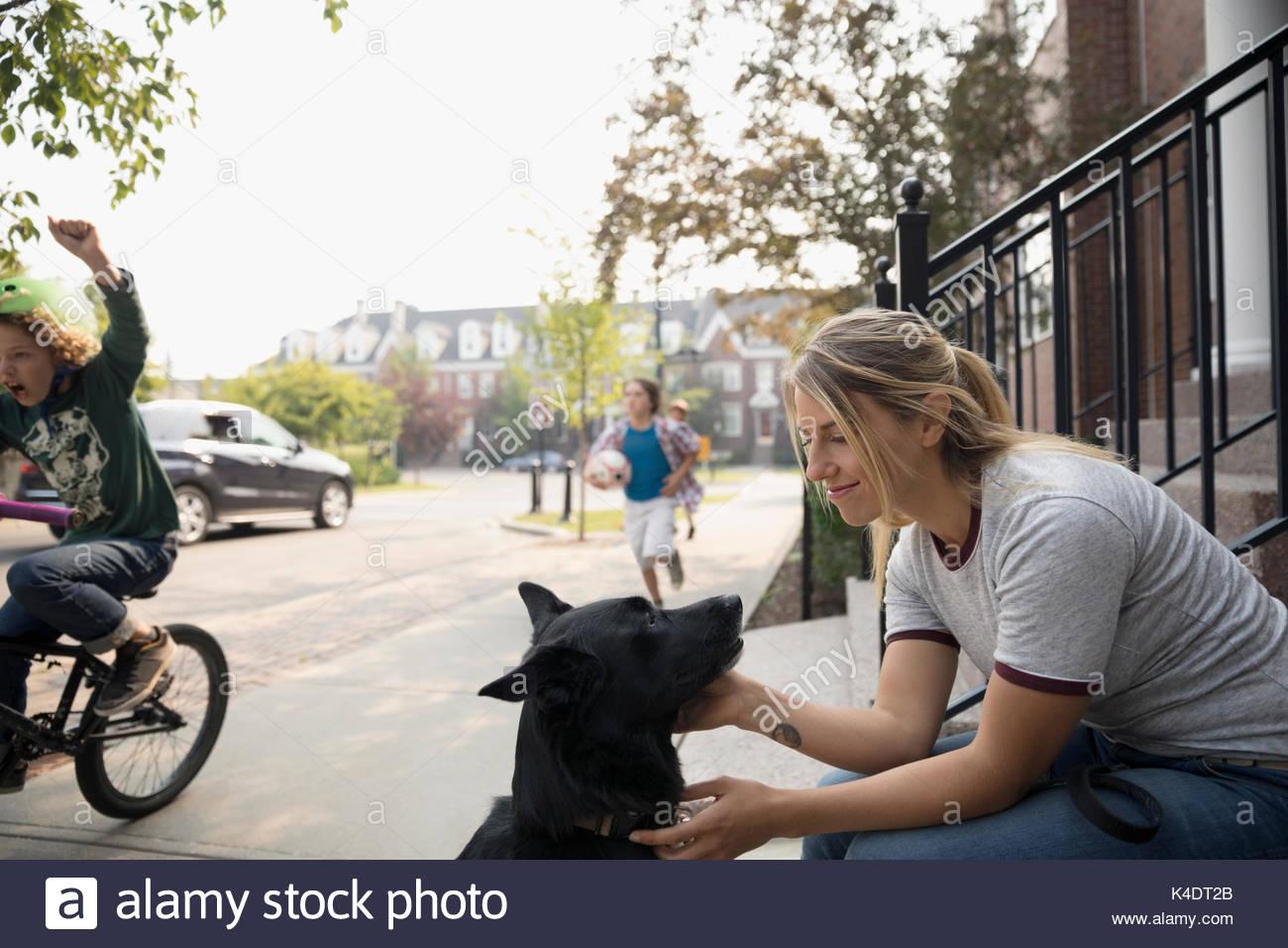 Smiling woman with dog on neighborhood sidewalk - Stock Image