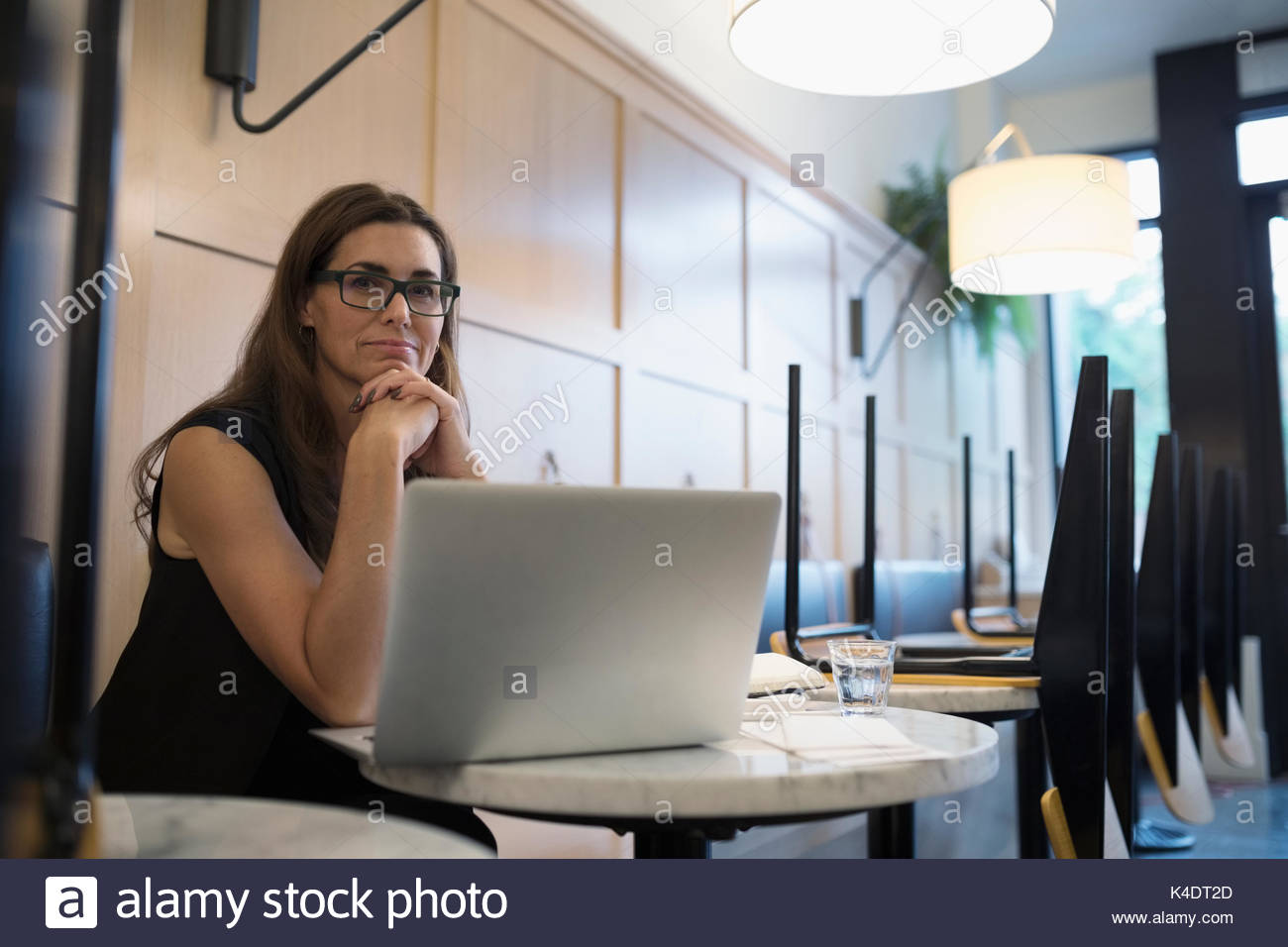 Portrait confident female cafe owner working at laptop at table - Stock Image
