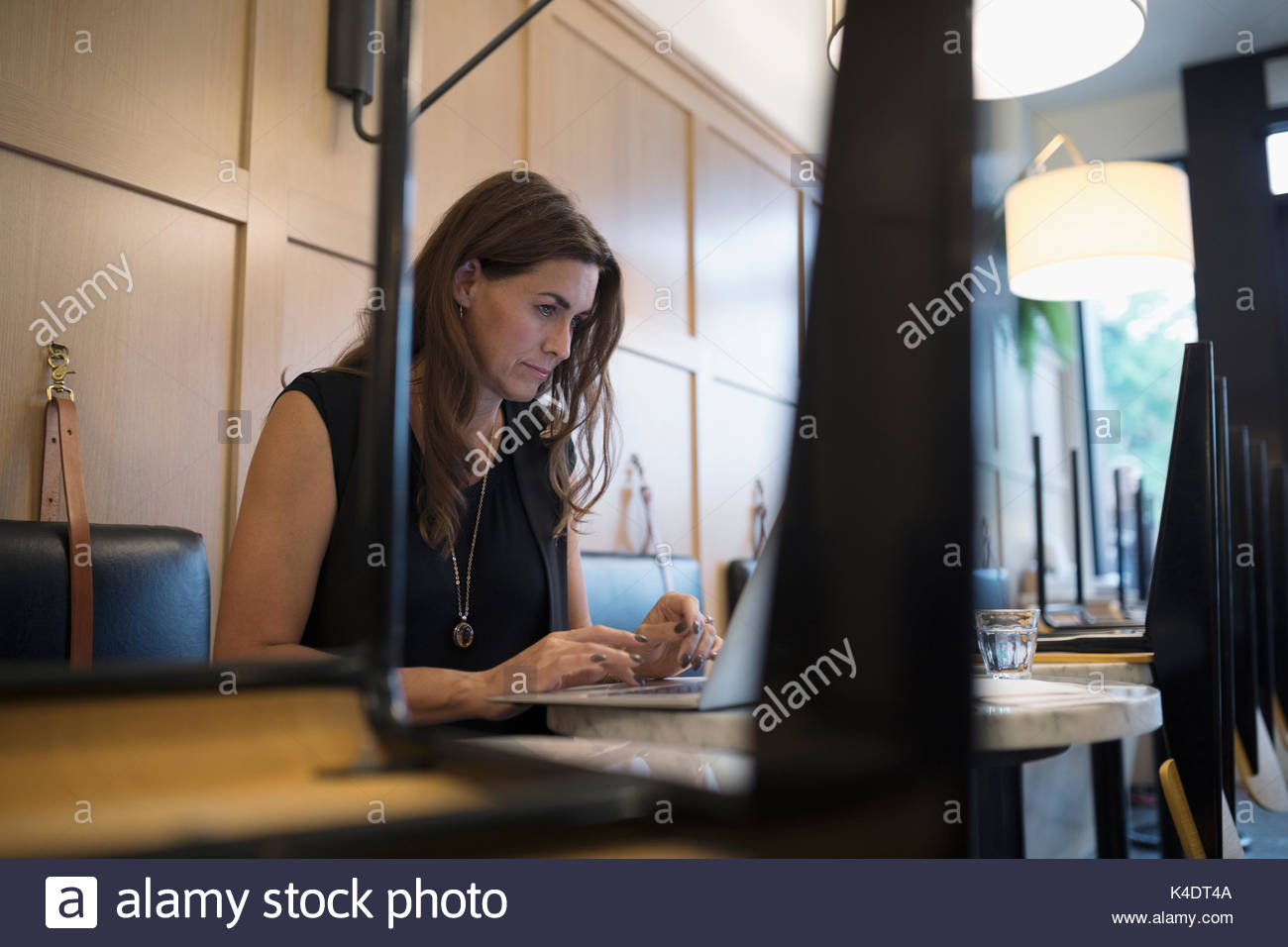 Focused female cafe owner working at laptop at table - Stock Image