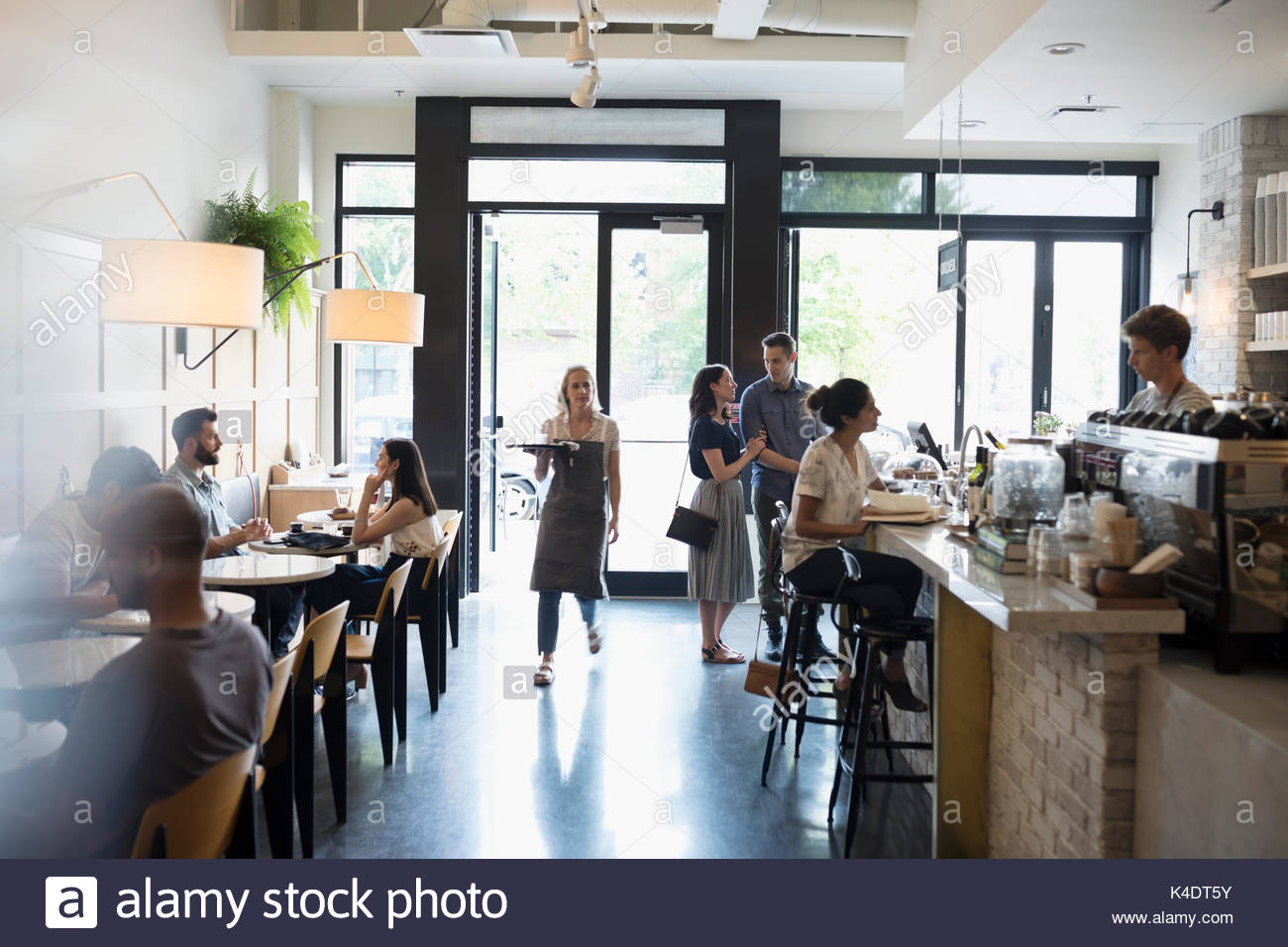 Waitress and customers in cafe - Stock Image