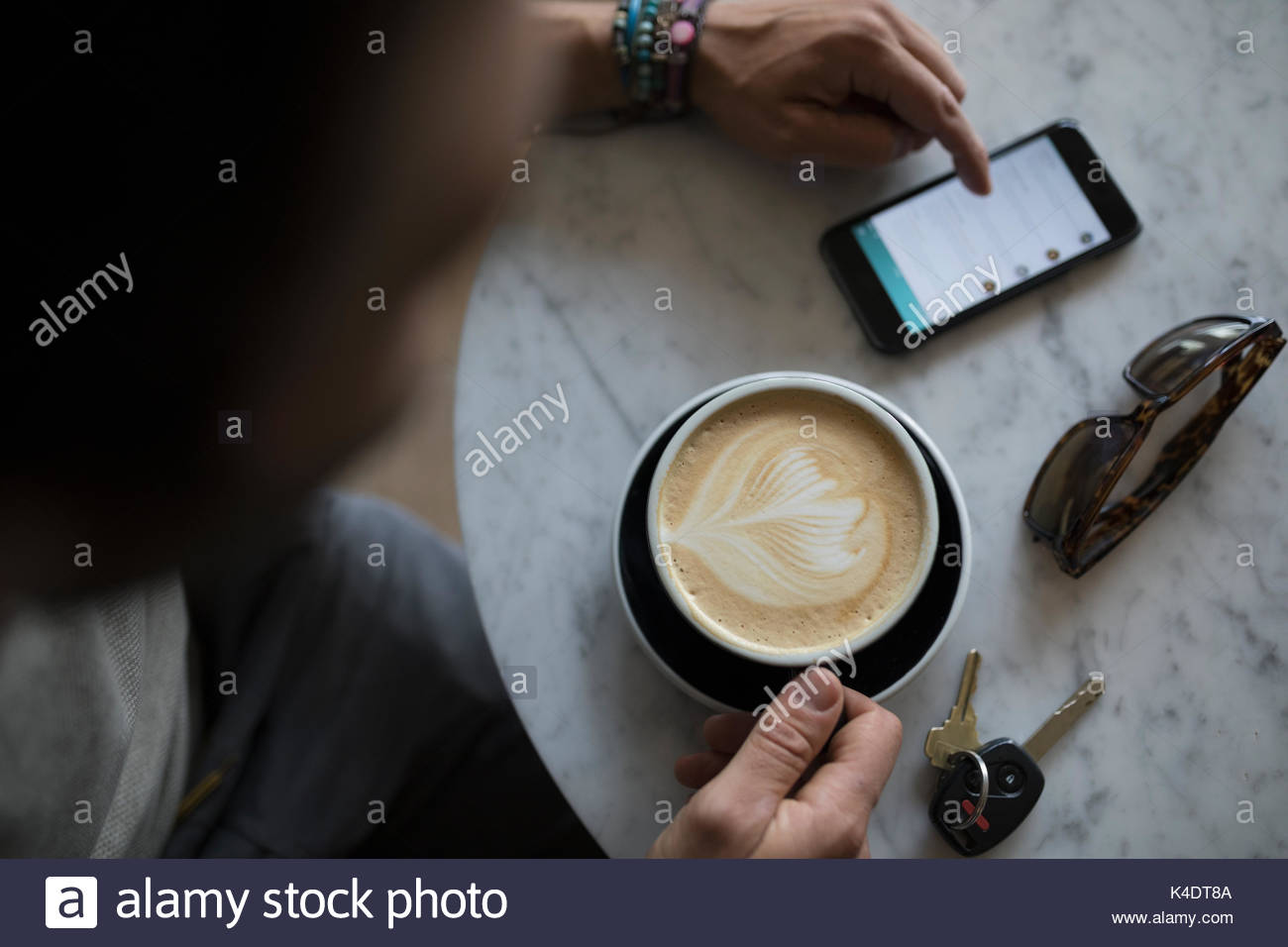 Overhead view man drinking cappuccino with milk foam leaf pattern and using smart phone in cafe - Stock Image