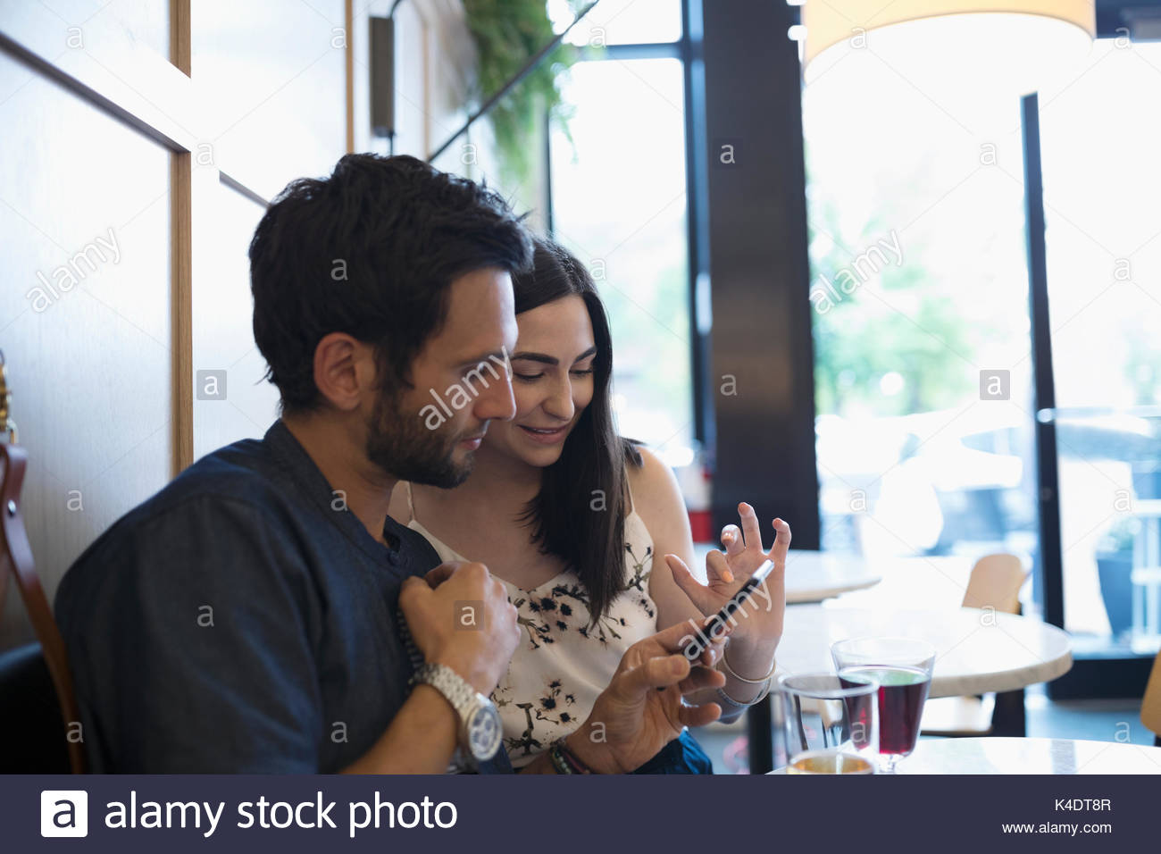 Couple using cell phone at cafe table - Stock Image