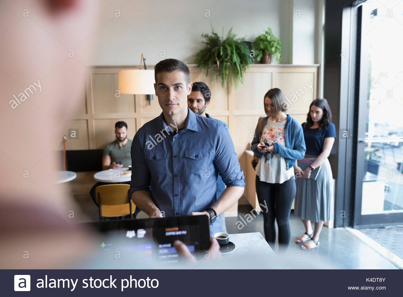 Customer ordering at cafe counter - Stock Image