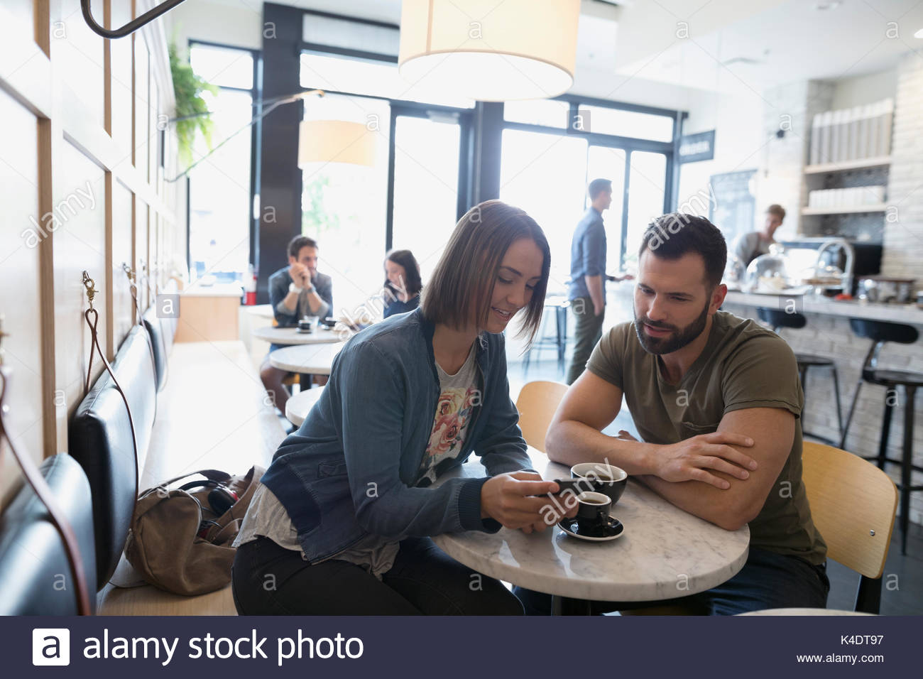 Couple drinking coffee and using cell phone in cafe Stock Photo