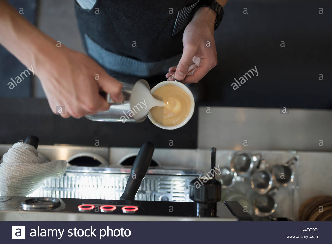 Overhead view male barista pouring milk foam into cappuccino in cafe - Stock Image