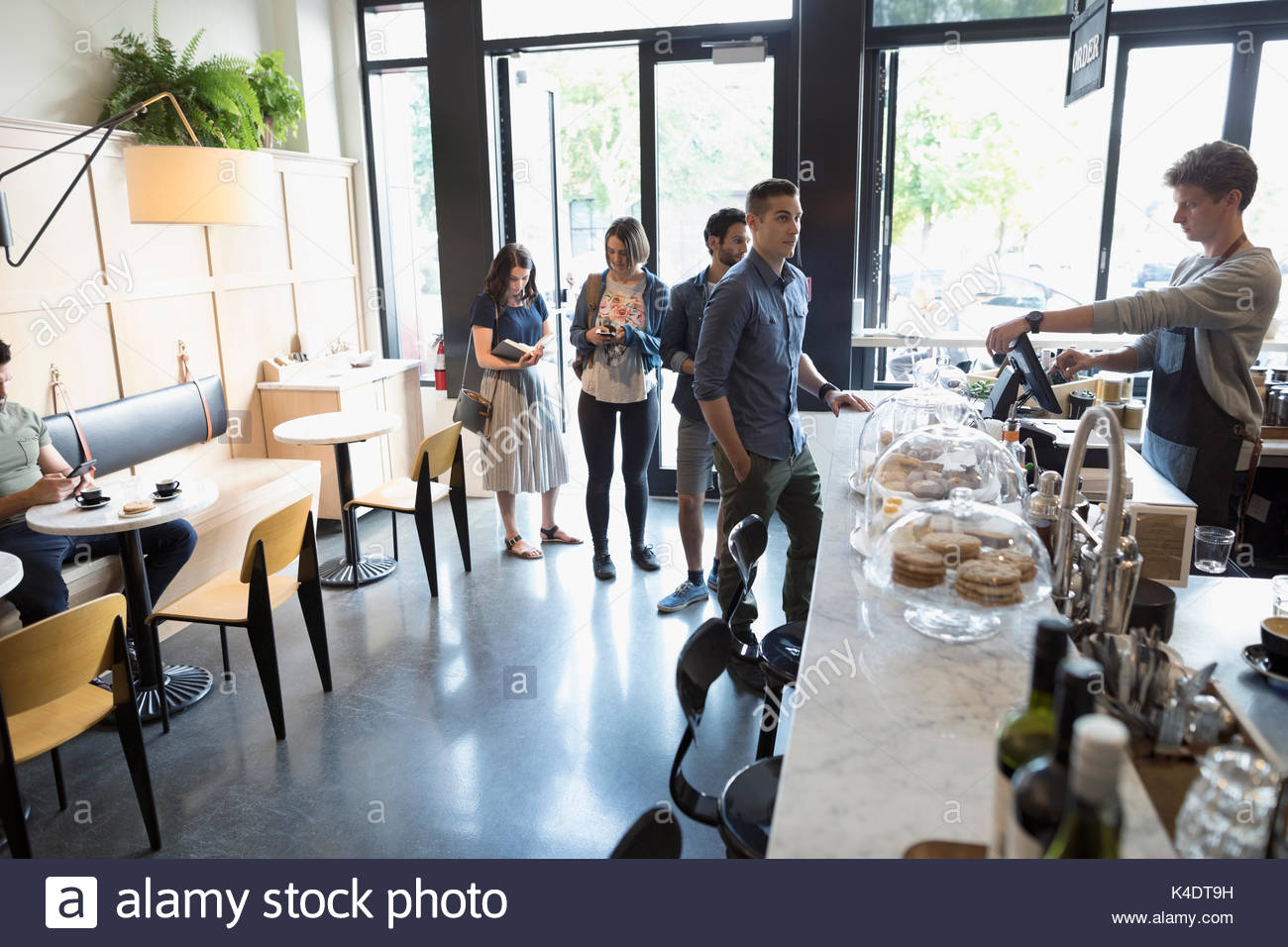 Male worker helping customers in queue at cafe counter - Stock Image