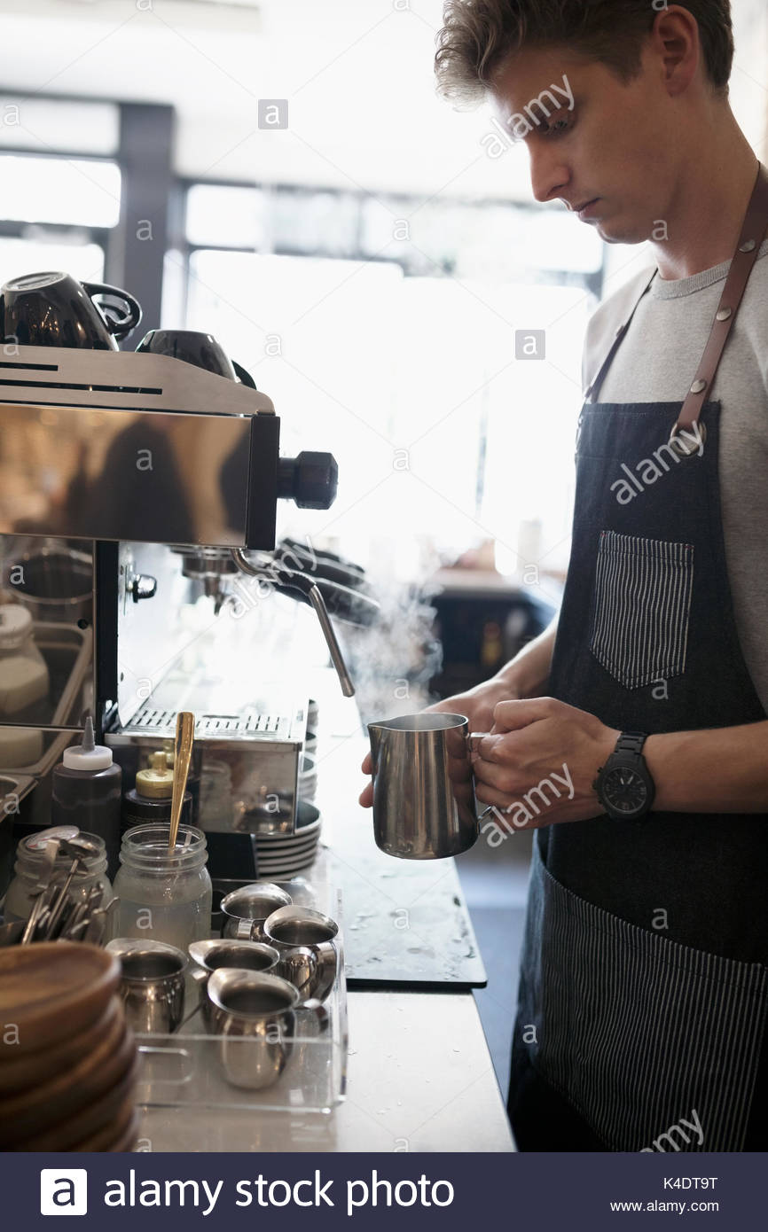 Male barista steaming milk at espresso machine in cafe - Stock Image