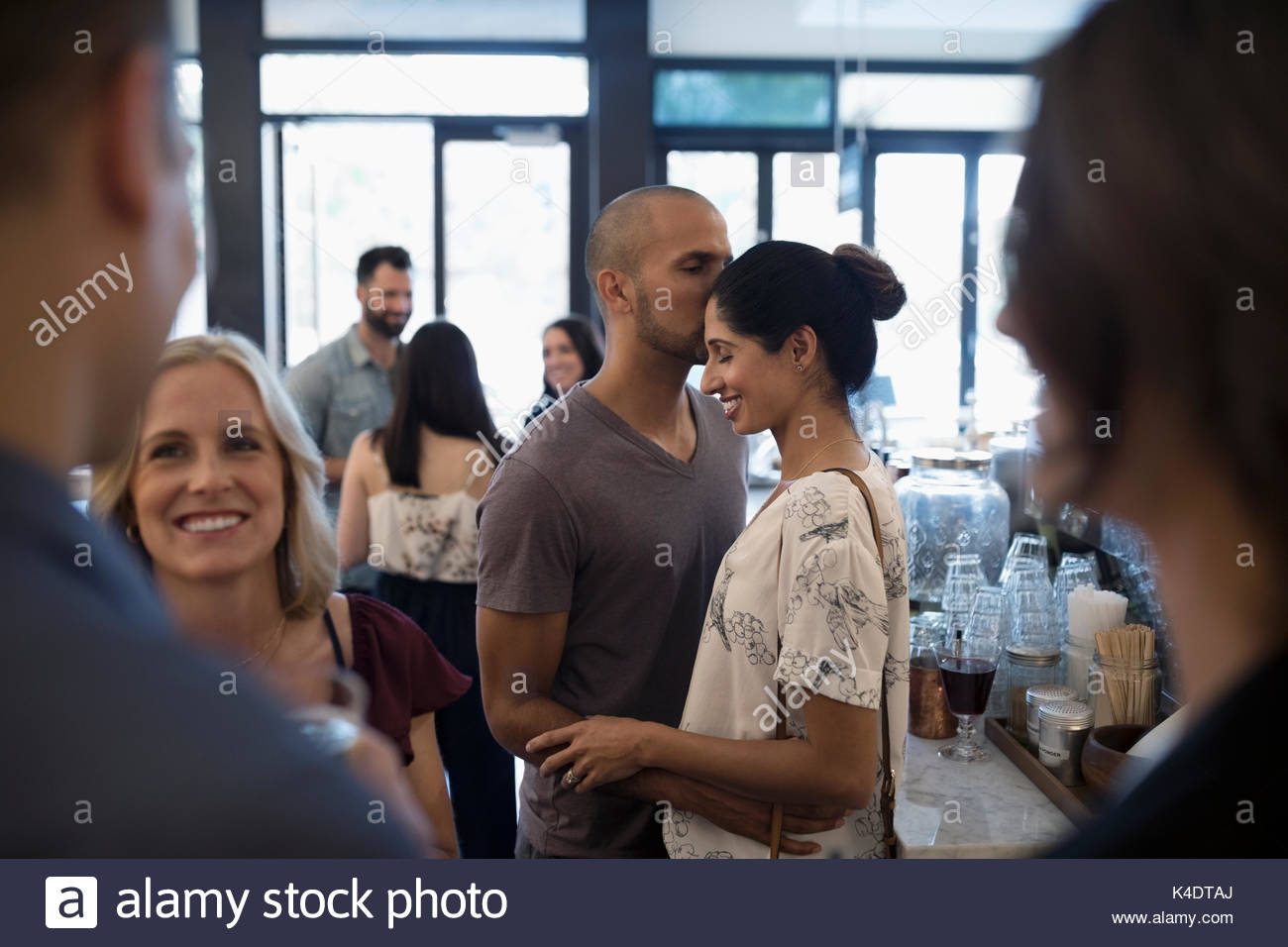 Affectionate couple kissing in bar - Stock Image