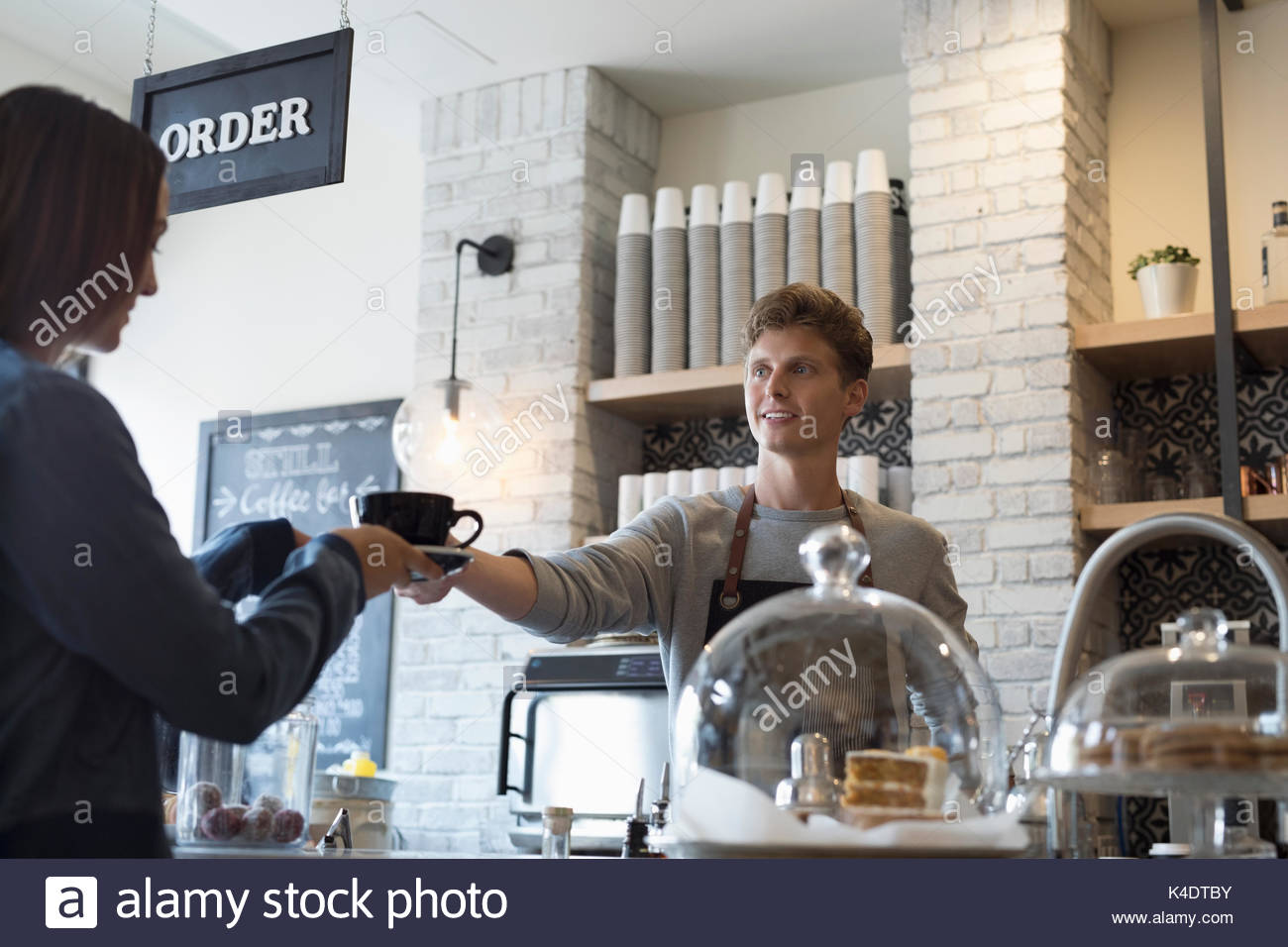 Male barista serving coffee to female customer in cafe - Stock Image