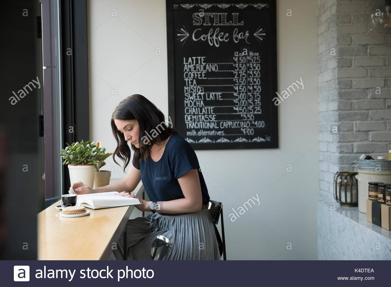 Woman reading book and drinking coffee at counter in cafe - Stock Image