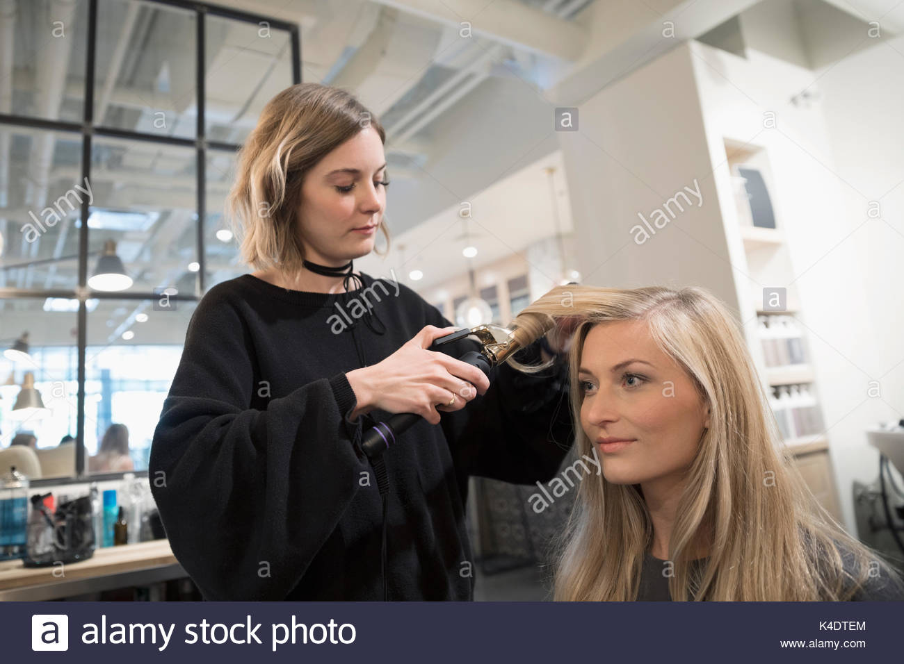 Female hair stylist curling hair of customer with curling iron in hair salon - Stock Image