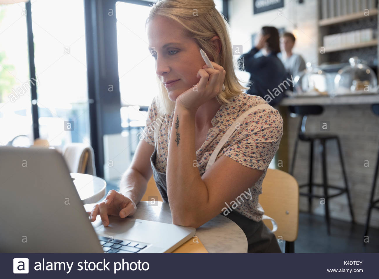 Female cafe owner working at laptop - Stock Image
