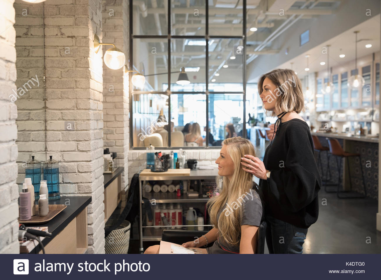 Female hair stylist and customer talking, planning in hair salon - Stock Image