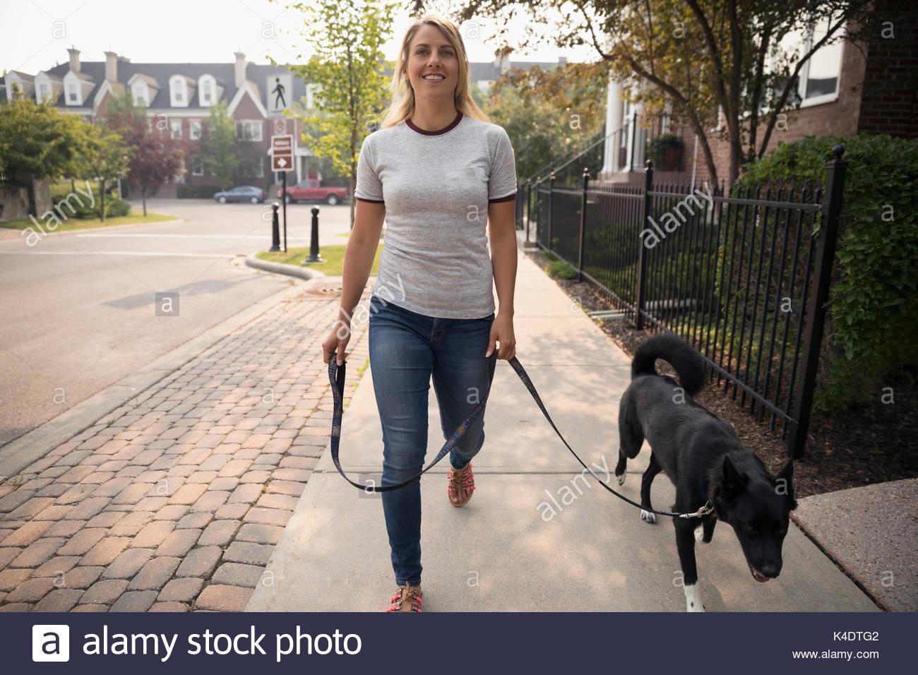 Smiling woman walking dog on leash on neighborhood sidewalk - Stock Image