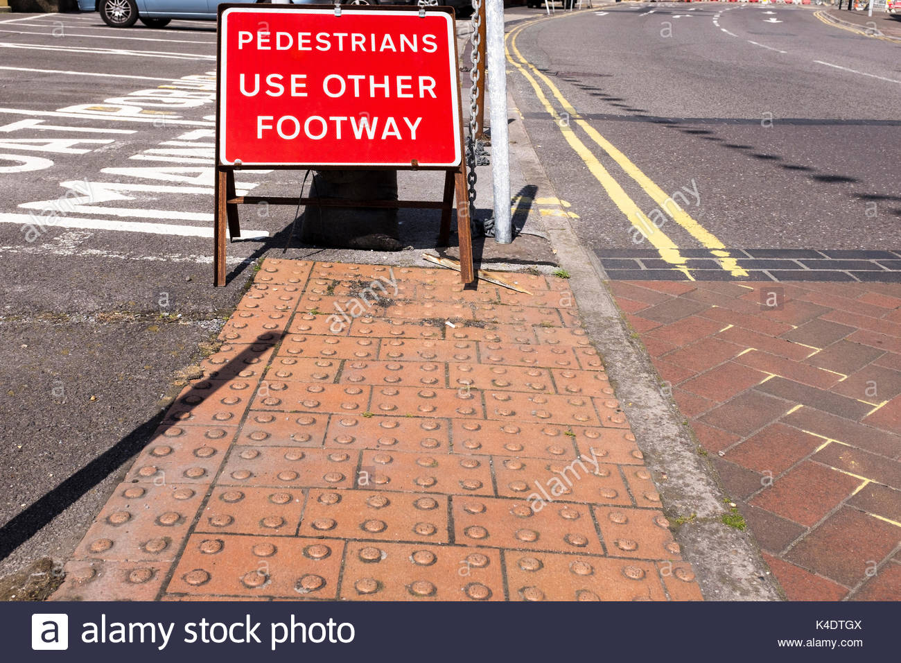 Tactile paving to assist those with visual impairment by road crossing point and Pedestrians Use Other Footway sign, Poole, Dorset, England, UK Stock Photo