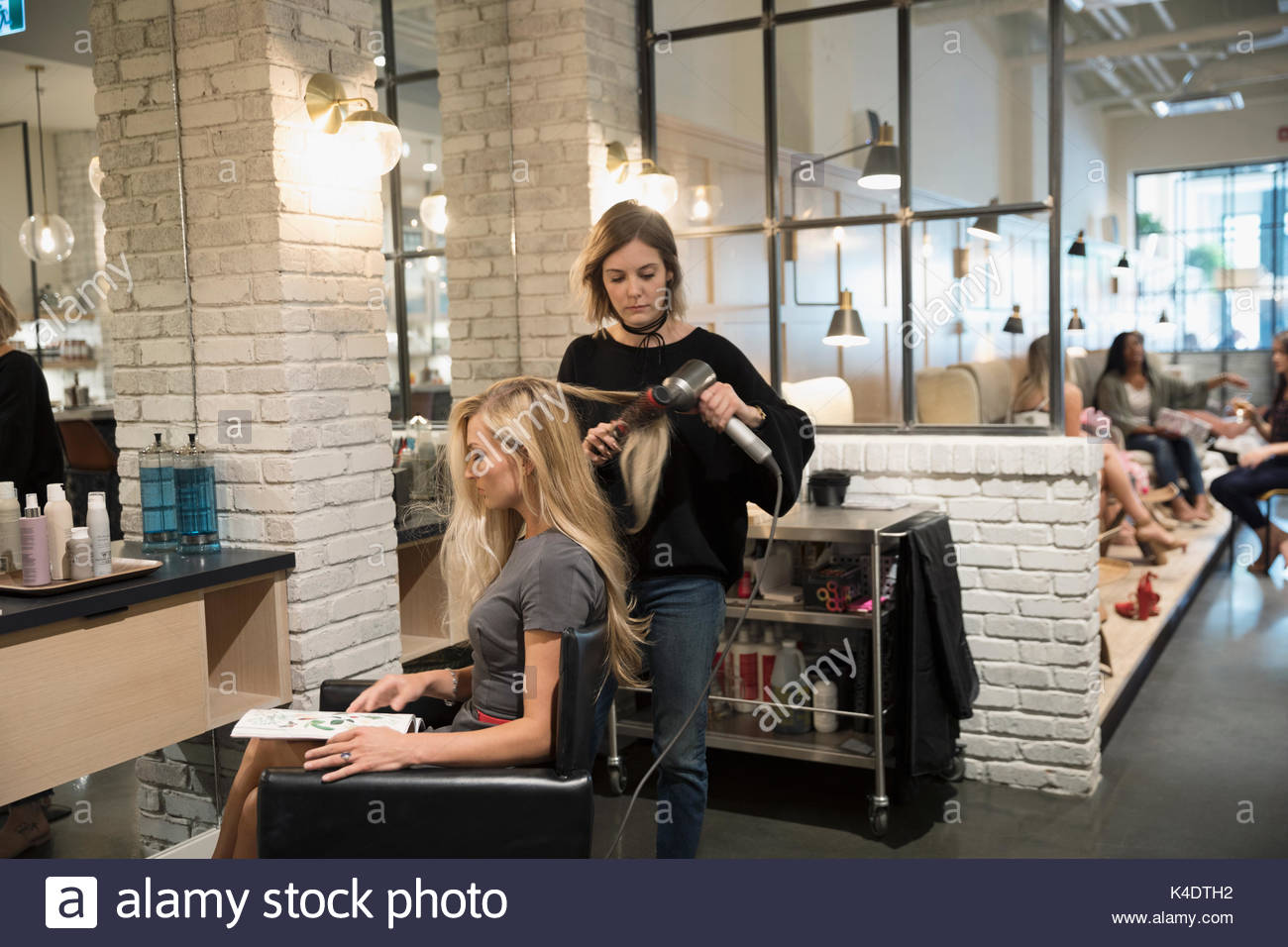 Female hair stylist blow drying hair of customer in hair salon - Stock Image