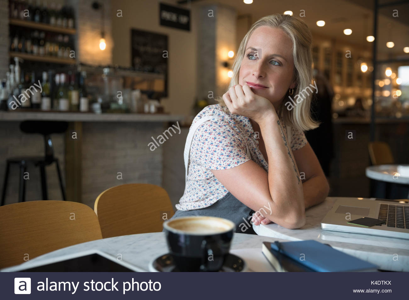 Smiling pensive woman using laptop, looking over shoulder in cafe Stock Photo