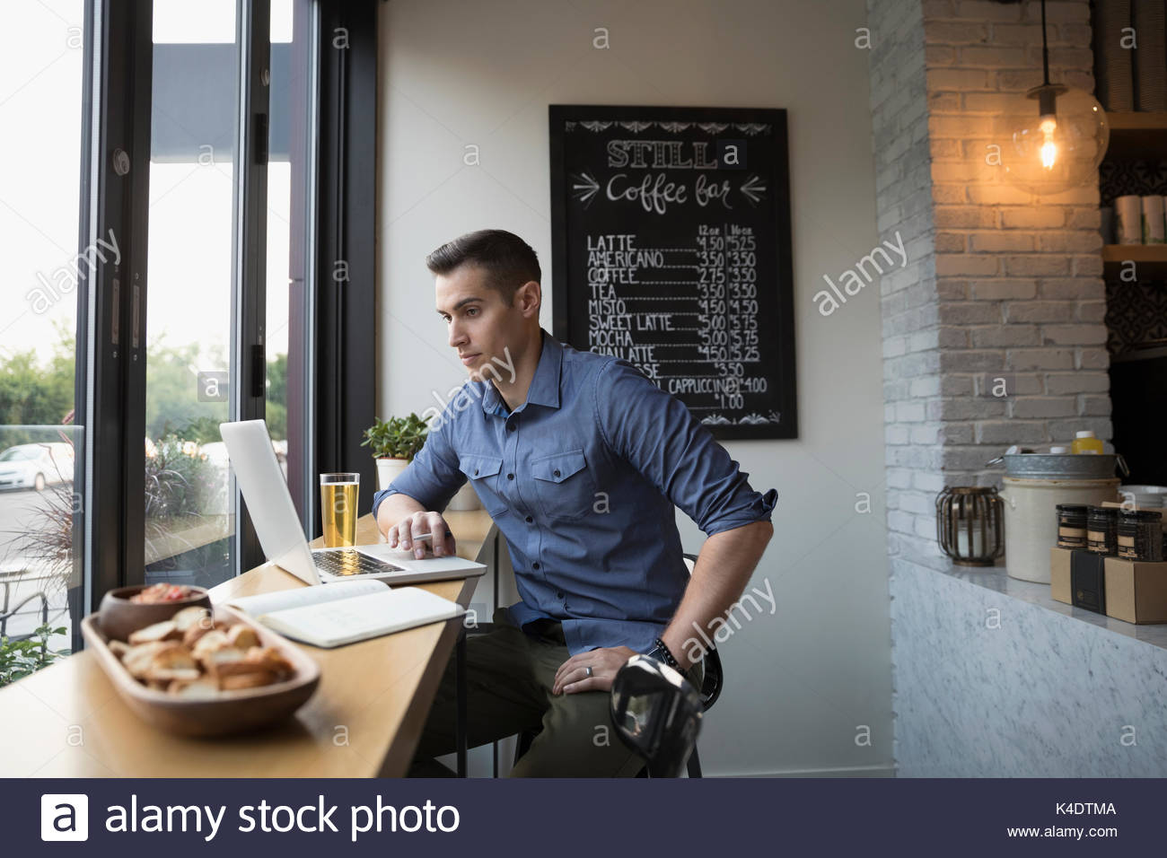 Man drinking beer and using laptop at cafe window - Stock Image