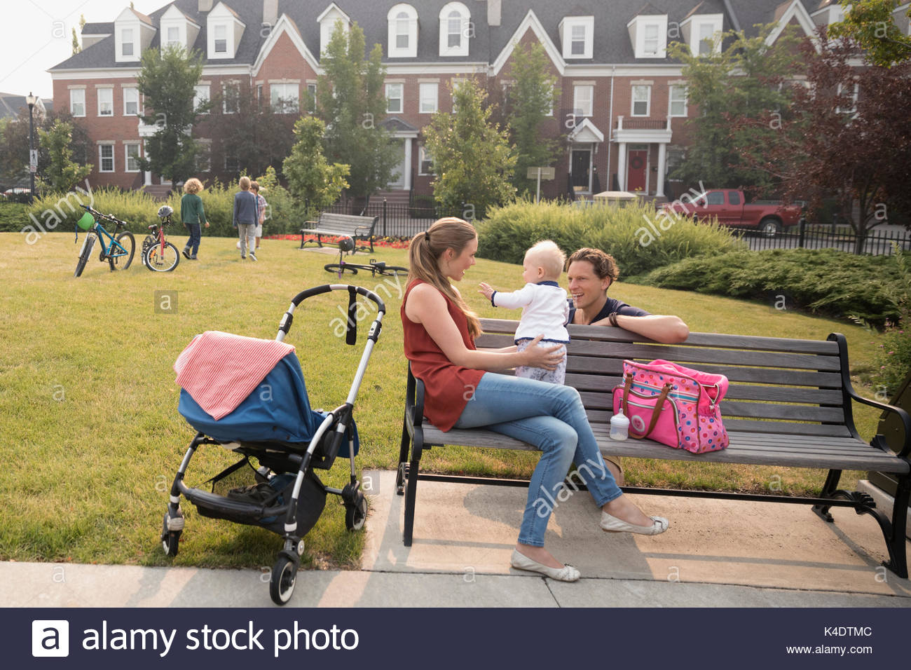 Young family with baby sitting on neighborhood park bench - Stock Image