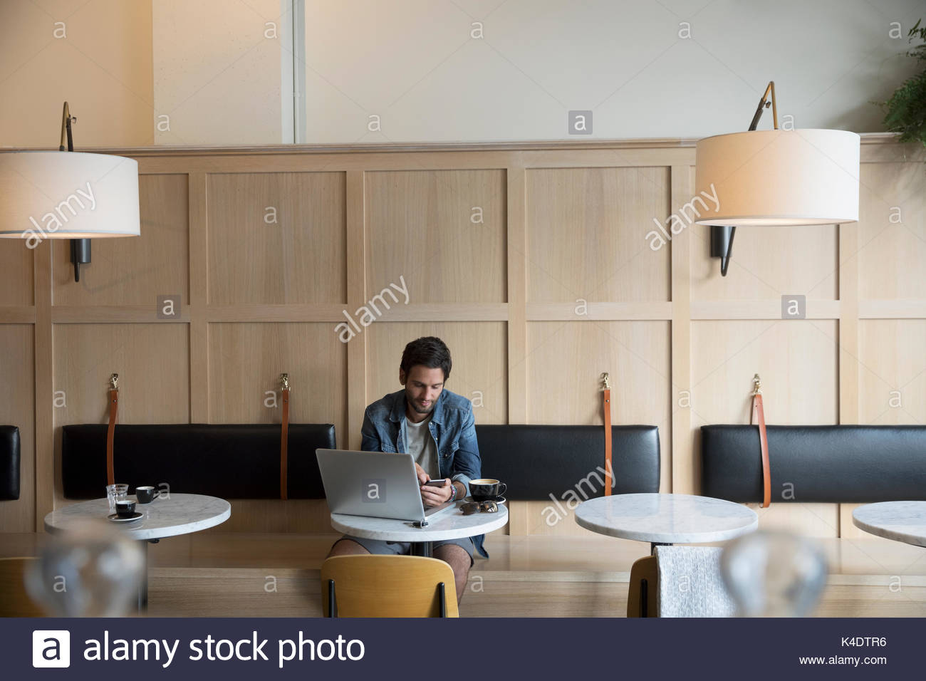 Man texting with cell phone at laptop, drinking coffee in cafe - Stock Image