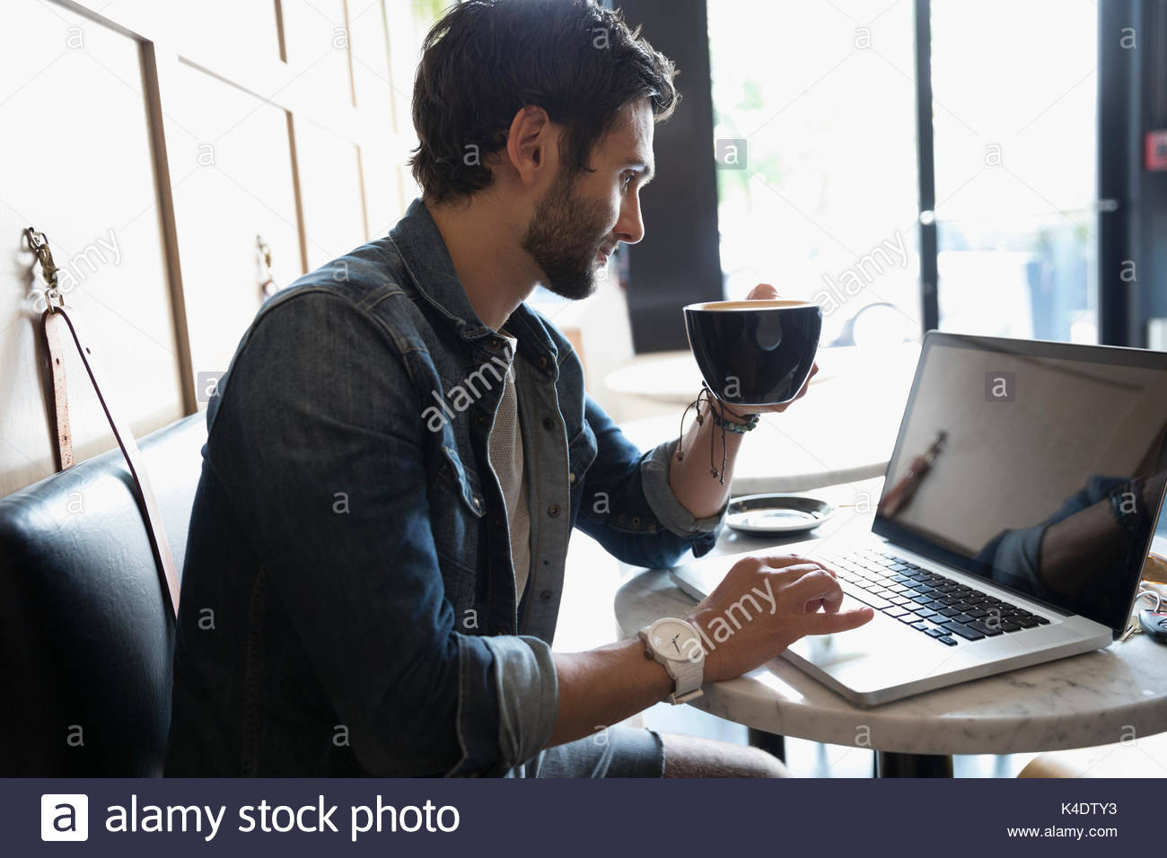 Man using laptop and drinking coffee in cafe - Stock Image