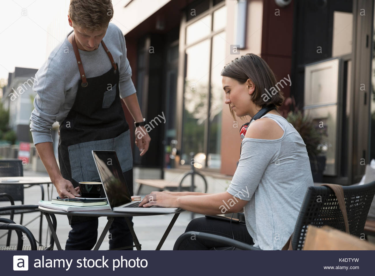 Waiter serving coffee to woman using laptop at sidewalk cafe - Stock Image