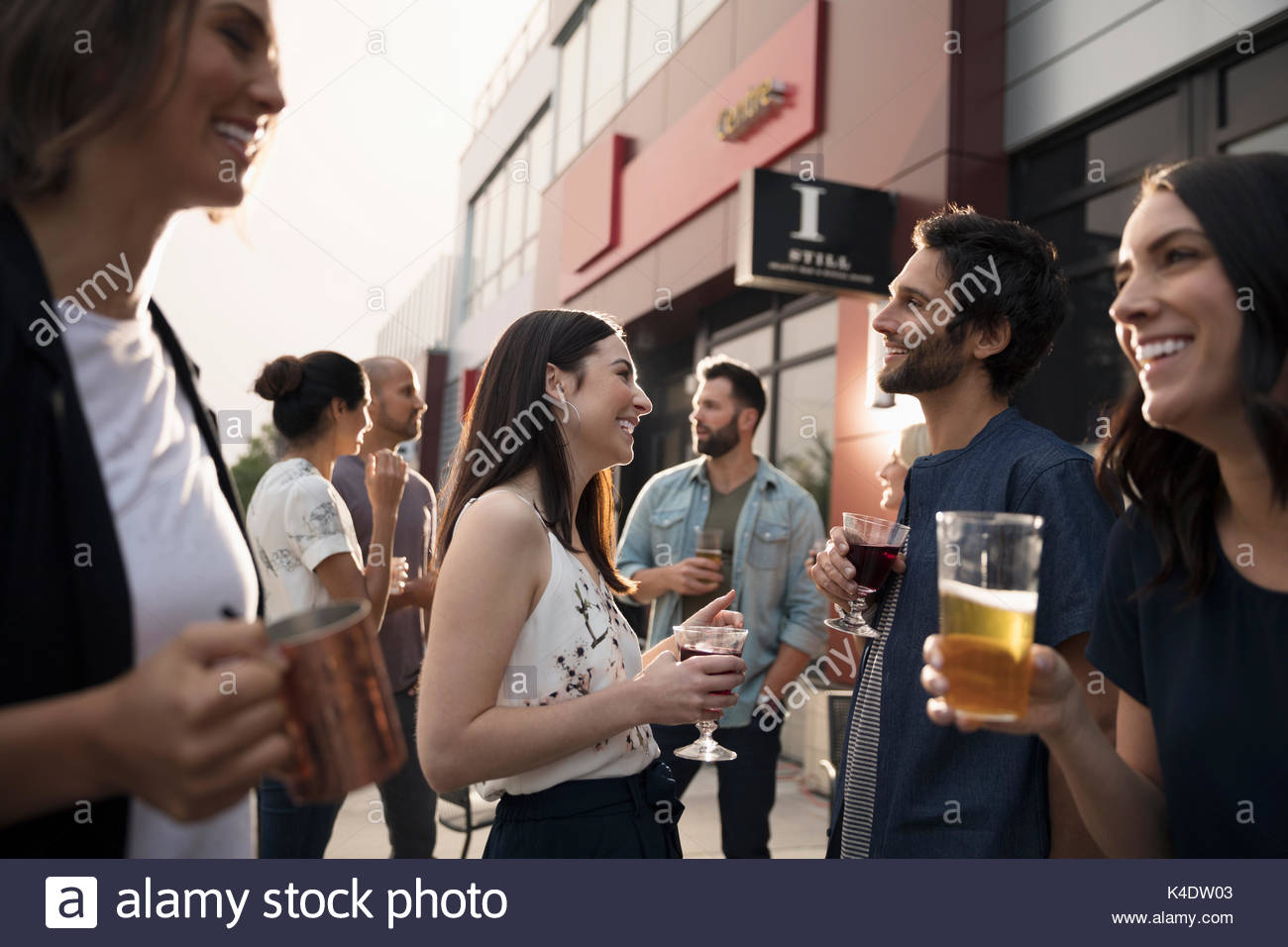 Friends drinking beer and wine, socializing on bar patio - Stock Image