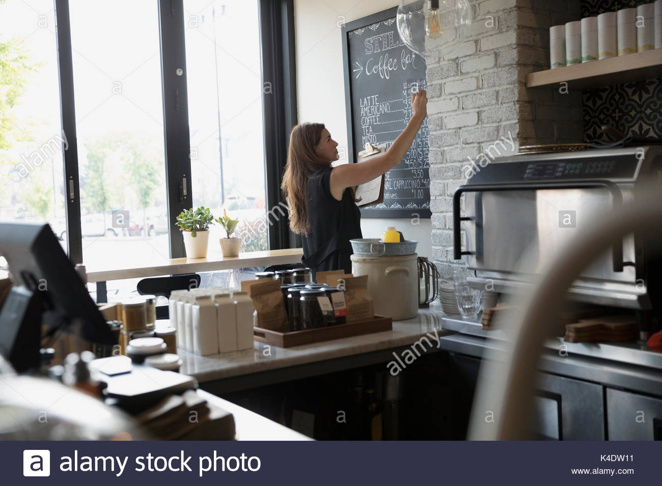 Female cafe owner writing menu and prices on blackboard - Stock Image