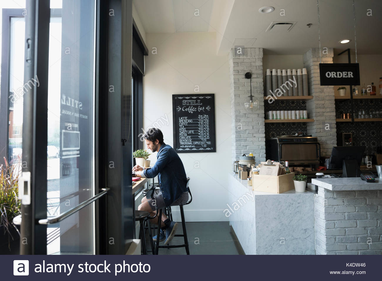 Man sitting in window at cafe - Stock Image