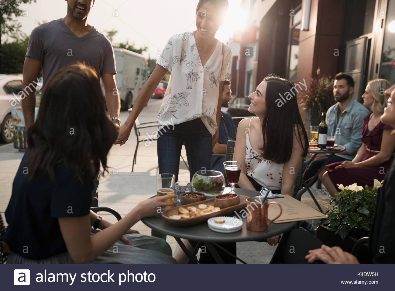 Woman greeting friends at sidewalk cafe - Stock Image