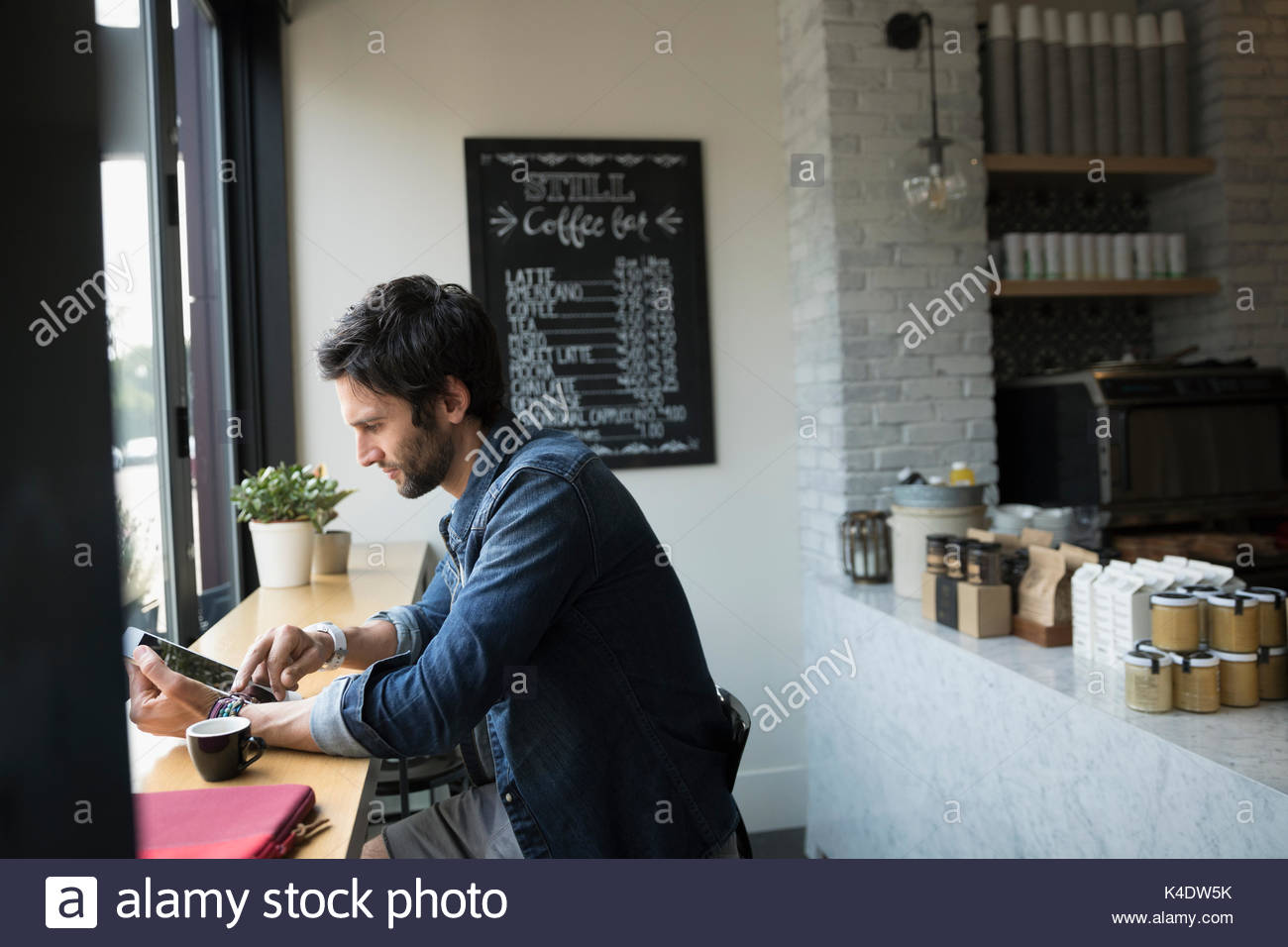 Man using digital tablet at cafe window - Stock Image