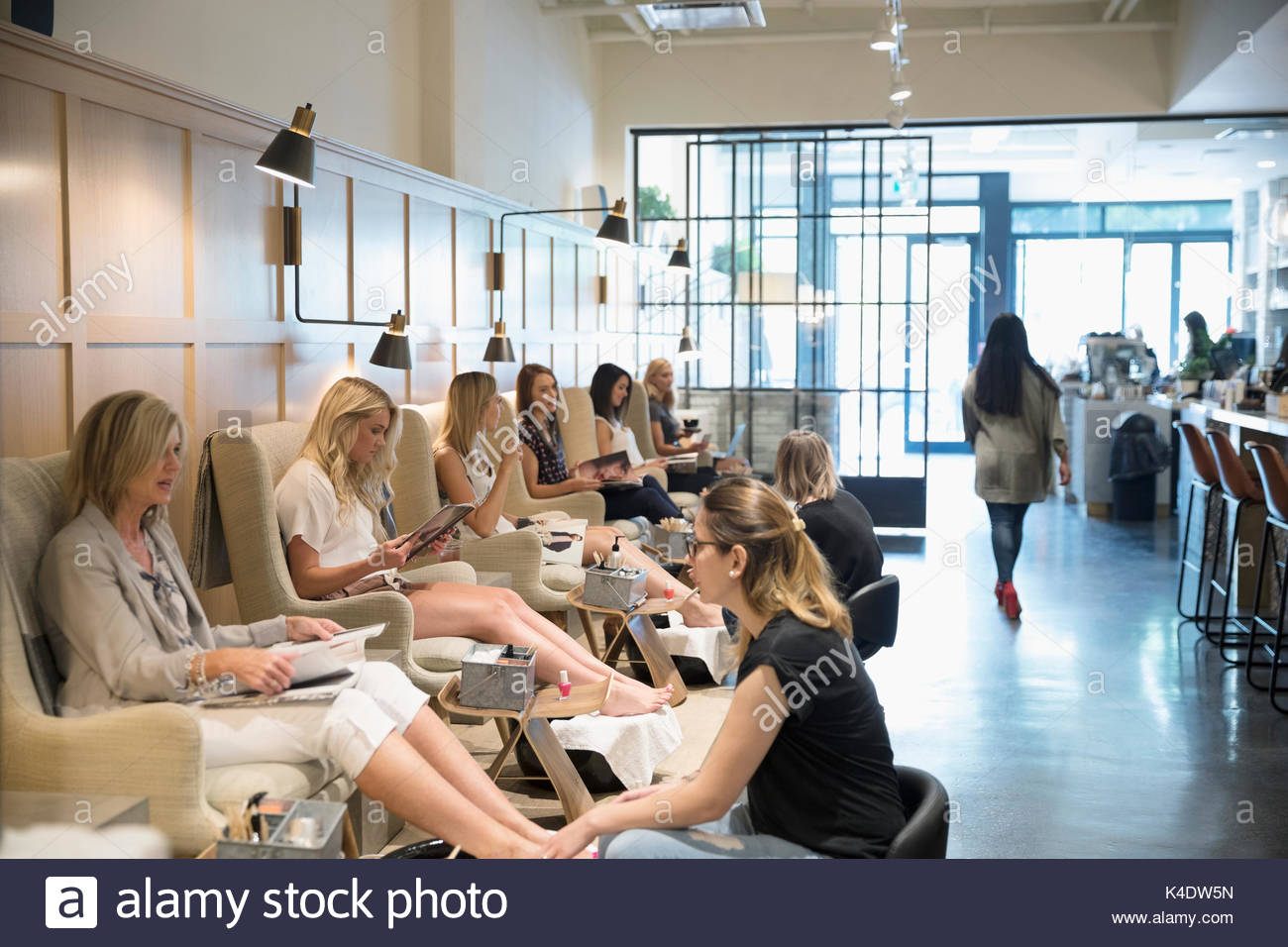 Female customers receiving pedicures at nail salon - Stock Image