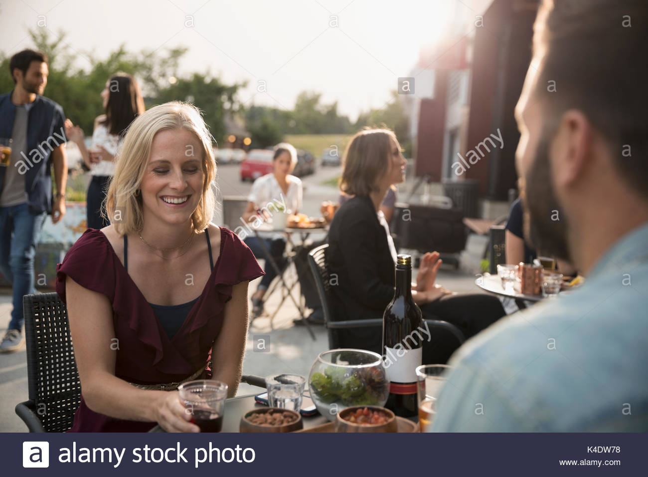 Smiling woman drinking wine with boyfriend at sidewalk cafe - Stock Image