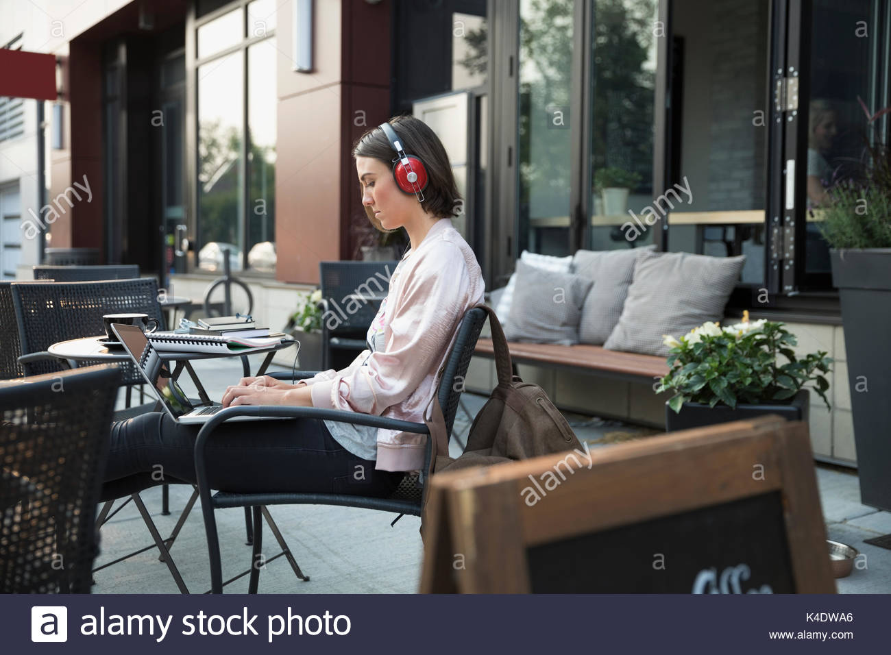 Brunette woman with headphones listening to music and using laptop at sidewalk cafe - Stock Image