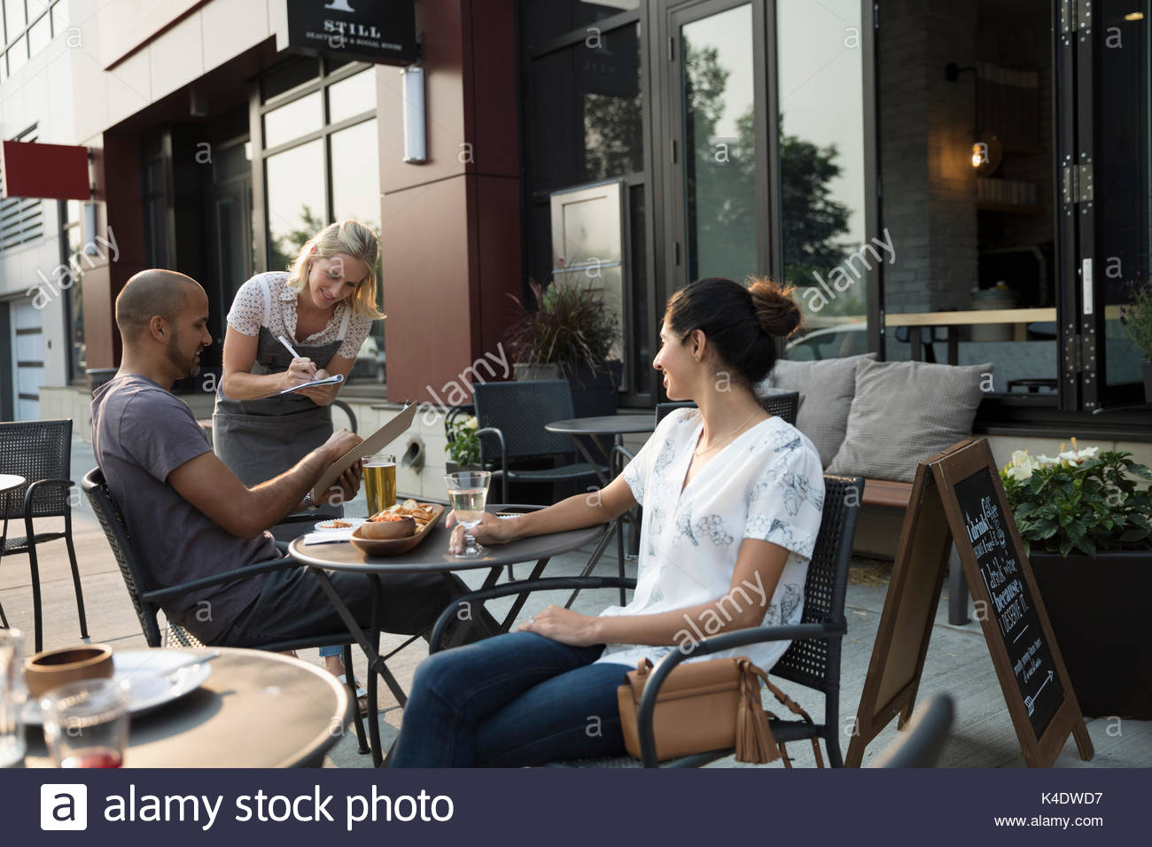Waitress taking order from couple at table at sidewalk cafe Stock Photo