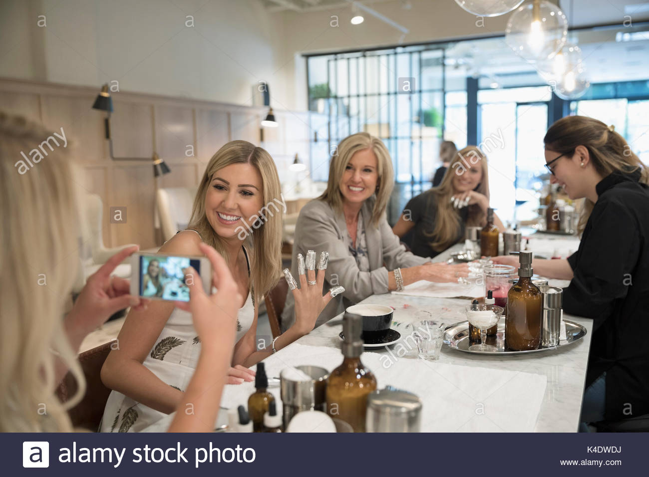 Smiling women friends getting gel manicures, posing for selfie in nail salon - Stock Image
