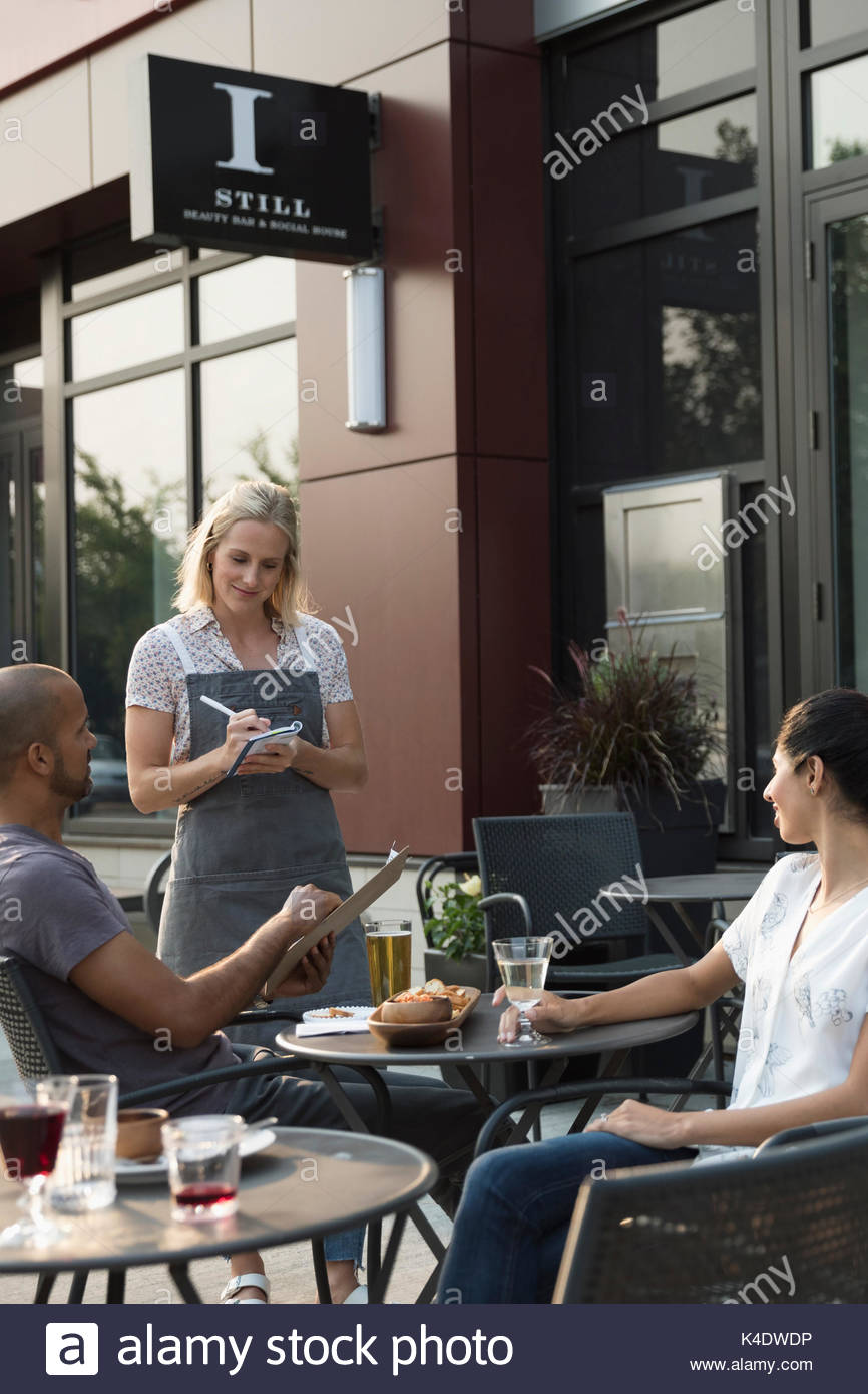 Waitress taking order from couple at table at sidewalk cafe - Stock Image