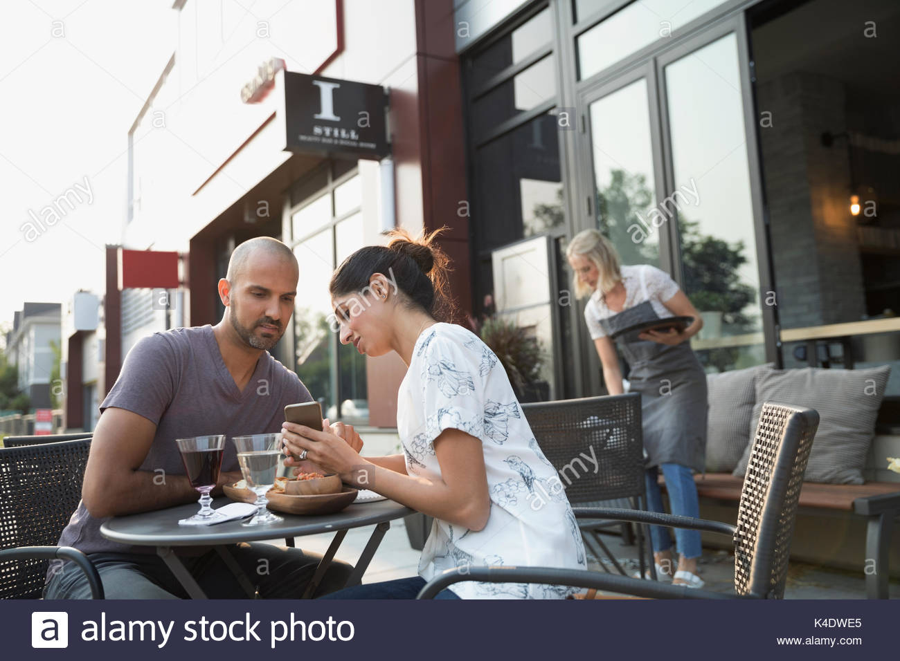 Couple drinking wine and using cell phone at sidewalk cafe - Stock Image