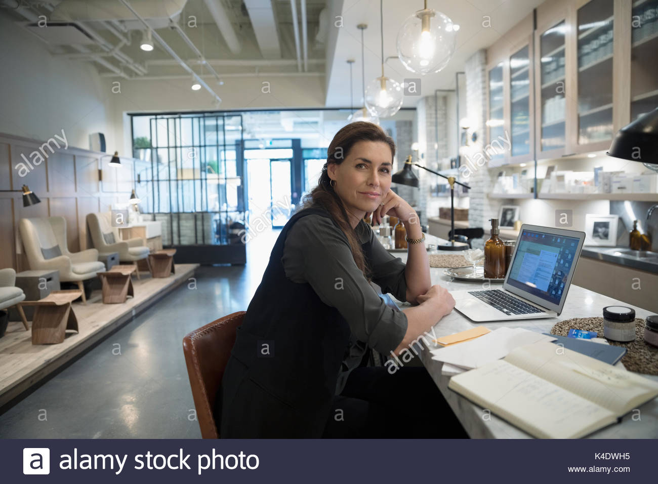 Portrait confident female nail salon owner working at laptop - Stock Image