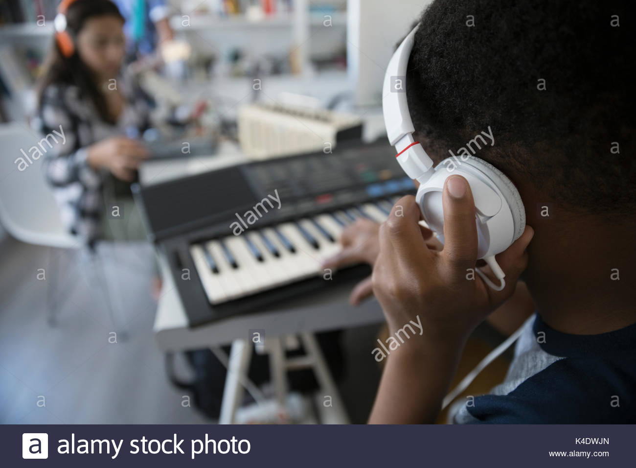 Teenage boy with headphones playing electric piano - Stock Image